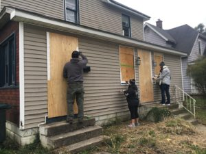 Volunteers Aimee Robertson-Fant, Kyle Johson, and Augusta Wray work to cover plywood securing the abandoned home at 710 N. Mulberry St.
