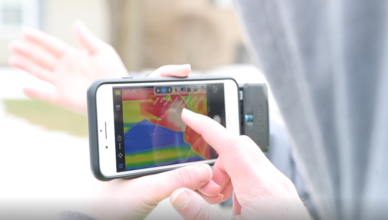 Student studying a thermal image on a cell phone